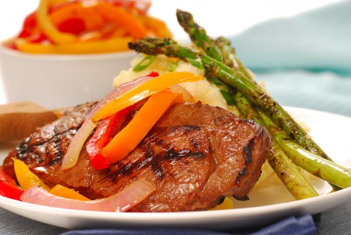 [Image: Beef entree prepared with fresh asparagus and bell peppers.]