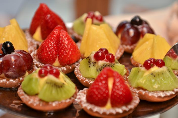 [Image: A platter that features a variety of our mini desserts all topped with fresh fruit.]